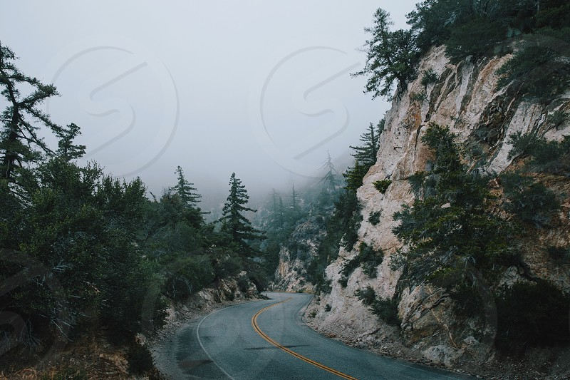 gray concrete road below cliff near trees below gloomy sky during daytime photo