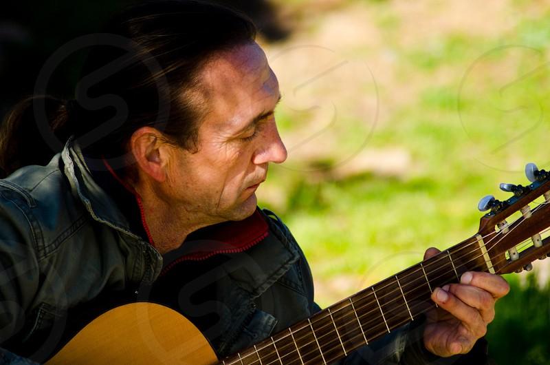 man in blue denim jacket playing brown acoustic guitar photo