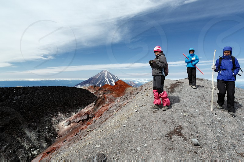 AVACHA VOLCANO KAMCHATKA PENINSULA RUSSIAN FAR EAST - AUGUST 7 2014: Three young women tourists walking on mountain hiking trail on summit crater of active Avachinsky Volcano. photo