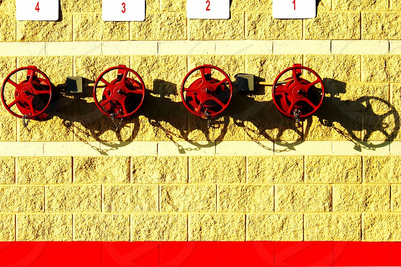 Four round red valves are on a yellow brick wall. photo