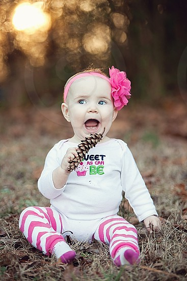 baby in white sweater holding a brown pine cone photo