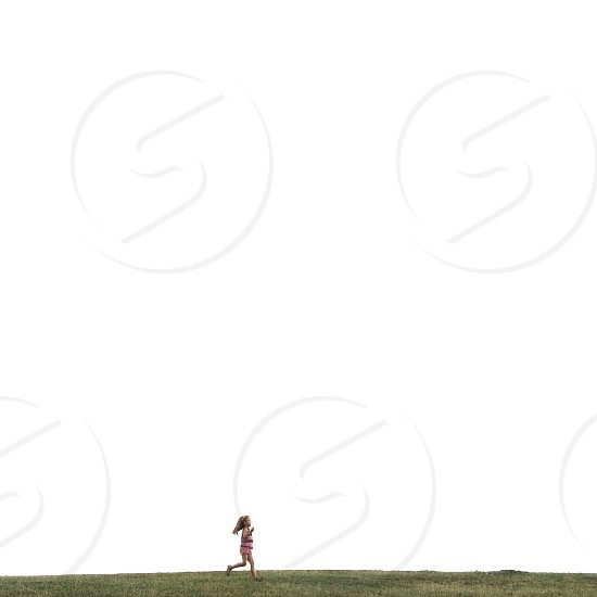 girl in red and white tank top running on the green fields photography photo