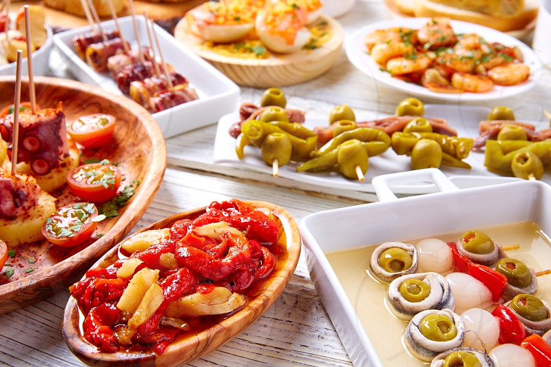 Tapas mix and pinchos food from Spain recipes also pintxos on a white wood board photo