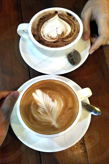 2 white ceramic coffee cup with latte art photo