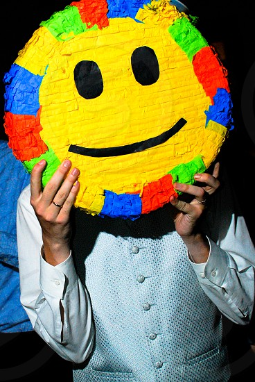 person holding a yellow smiley photo