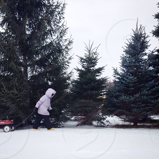 person in white jacket walking on snow photo
