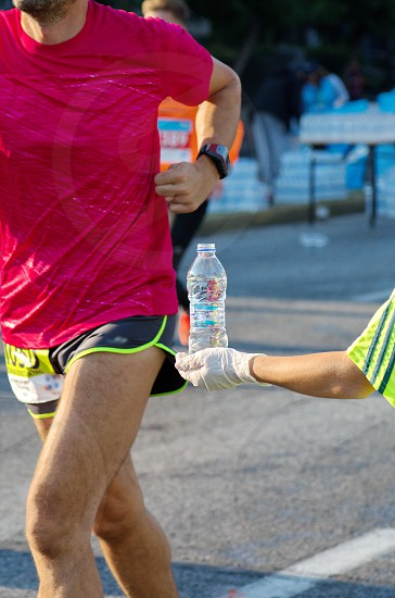 Volunteer offering a bottle of water to an athlete photo