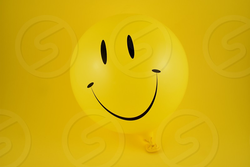 Happy emoji balloon. Yellow balloon photo. Smiley inflatable balloon isolated on a yellow background. Laughing party balloon photo