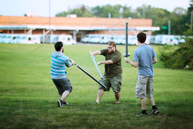 3 men doing sword fight photo