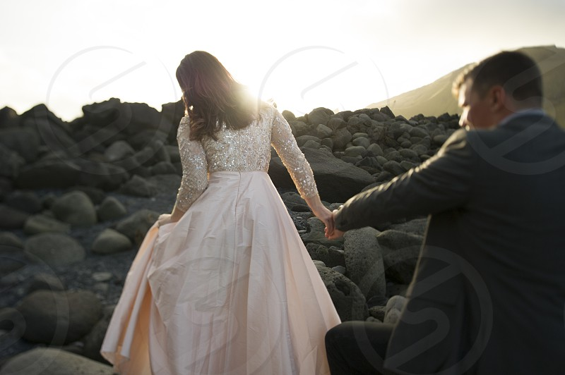 Bride and groom hiking up rocky hill in Iceland photo