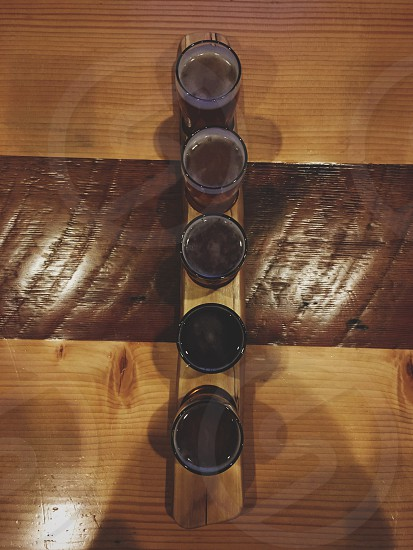 brown wooden base clear glass 5 candle holder on wooden table photo
