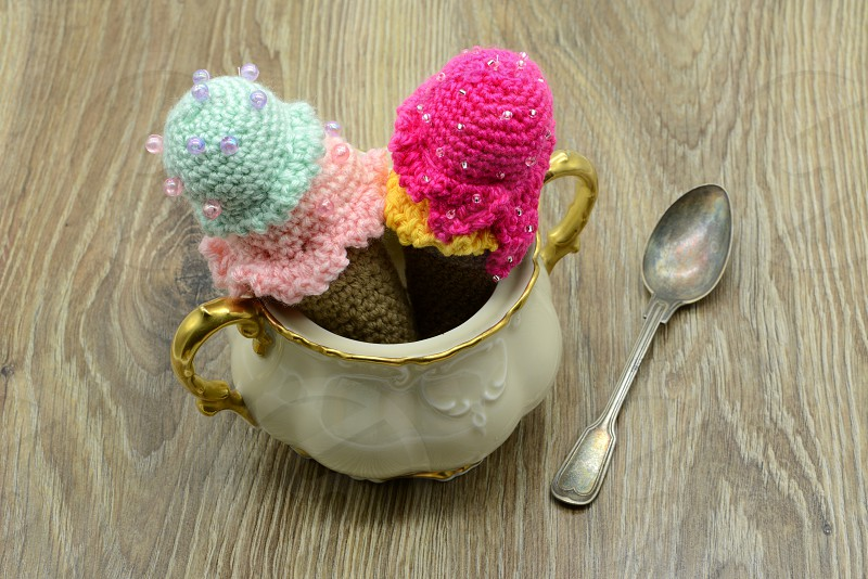 crochet ice cream cone in a sugar box with wool on table background photo