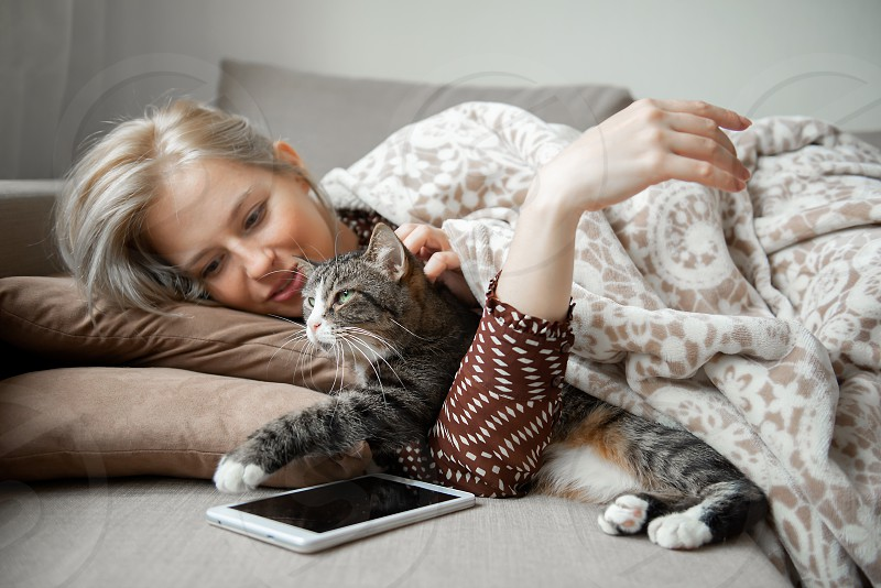 Young woman lying down on the couch with her cat photo