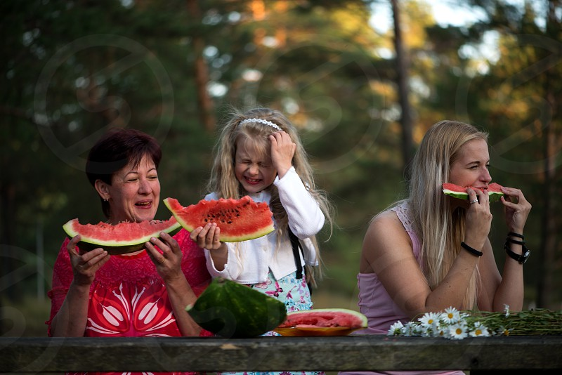 Mother and daughters eating watermelon photo