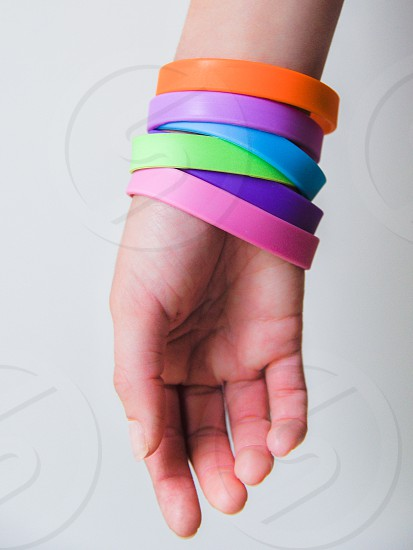 person's right hand with orange purple and green rubber band on the wrist photo