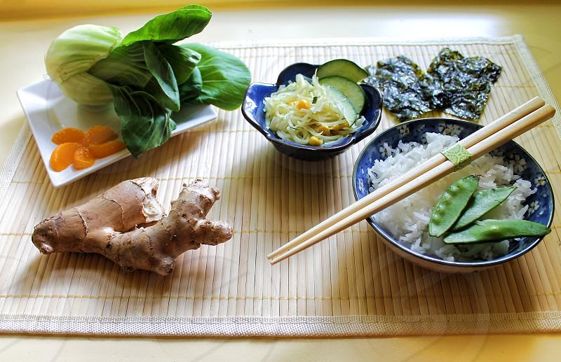 Asian food and chopsticks on a bamboo mat photo