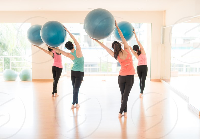 Fitness - Young Asia women doing sports training or workout with gymnastic ball in a gym Blue stability ball in female Pilates class rear mirror view photo