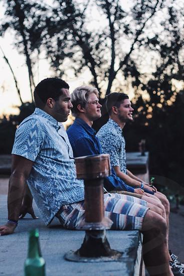 three man sitting on wall photo