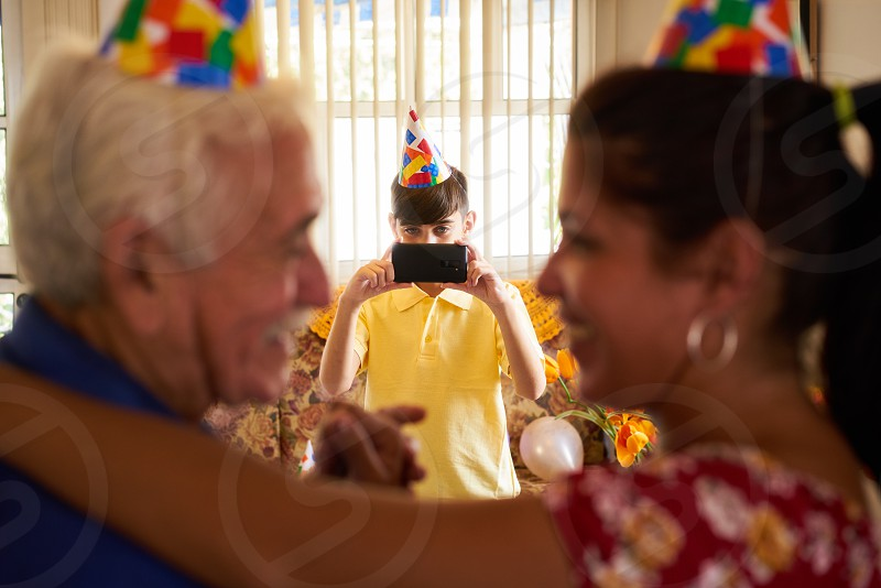Family celebrating senior man birthday in retirement home. Patient dancing with daughter in hospital and child taking photo. photo