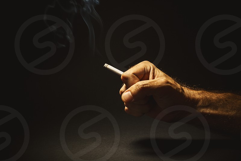 Conceptual composition about smoking studio shot of a man's hand holding a cigar.  photo
