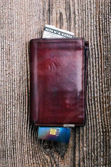 Leather wallet with dollar banknotes credit card on wooden desk. Portrait orientation photo