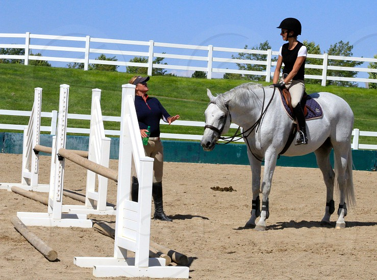 Trainer and hunter/jumper discussing the finer points of fence jumping with an eye toward precision.... photo