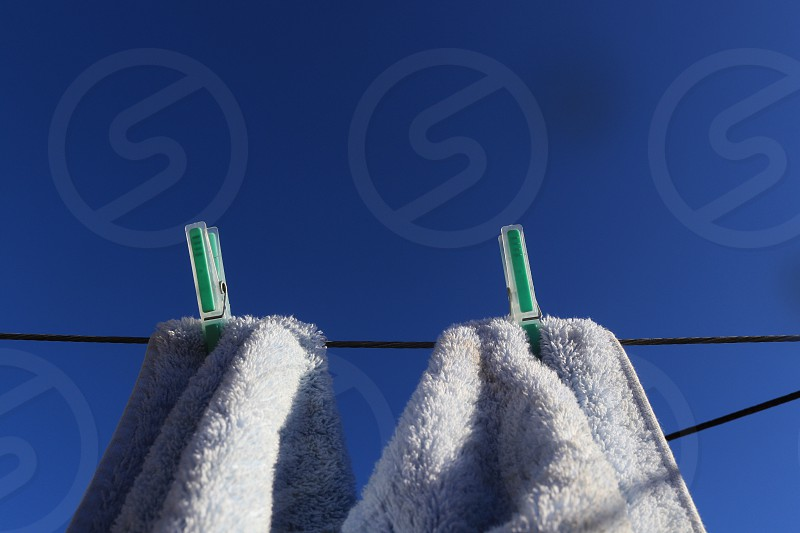 White terry cloth cotton bath towels hanging clothesline outdoors outside wind breeze sunny sunshine blue sky minimalism wash laundry clean angle creative background copy space text space clothespins clothes pegs plastic green backdrop high eye level day chore housework  photo