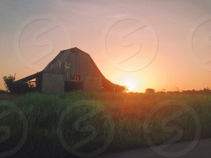 barn house on green grass field with sunrise view photo