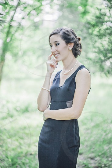 focus  photo of woman wearing black v neck sleeveless dress with white pearl necklace and bracelet near green trees during day time photo