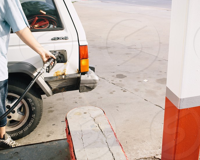 jeep cherokee 4x4 with human pumping gas into it photo
