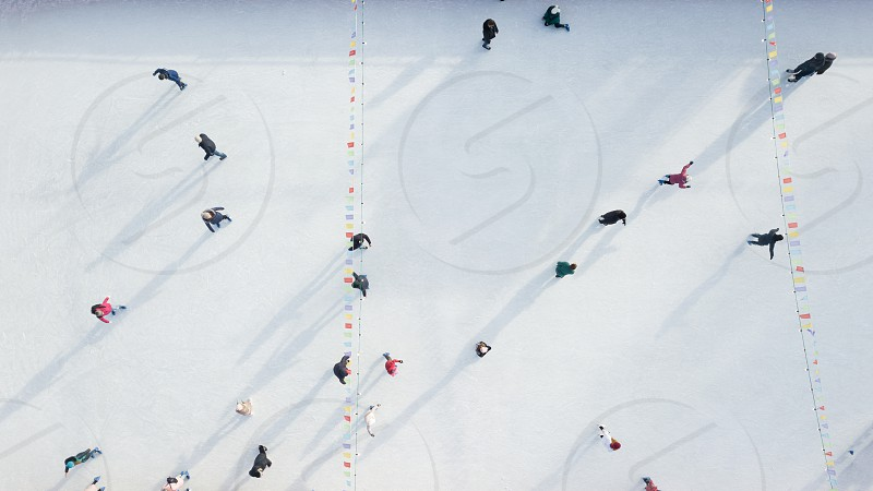Outdoor ice skating rink with people riding on a winter day. Aerial view from the drone. photo