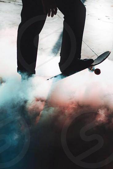 man playing skateboard with smoke photo