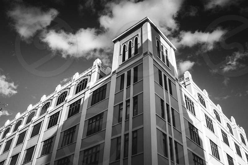 building under clouds and sky black and white photo photo