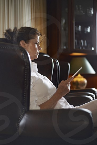 Affluent elderly woman sitting on a Chesterfield leather sofa reading the news on a tablet photo