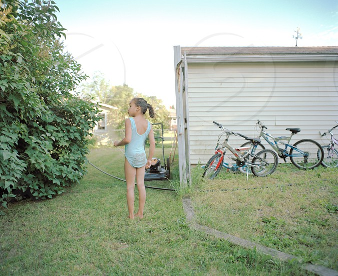 Girl wearing a blue bathing suit in the yard with bikes and shed photo