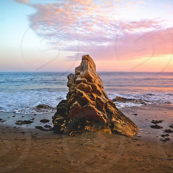 brown solitary stone in the beach photo