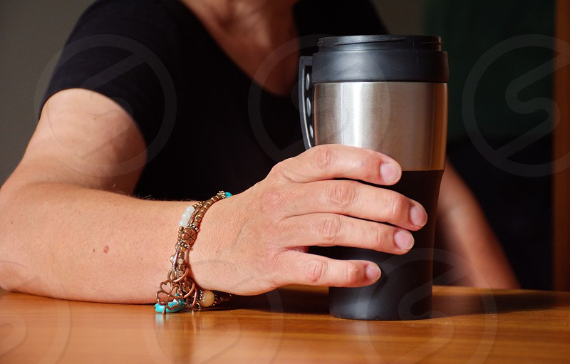 Closeup of woman's hand holding coffee cup photo