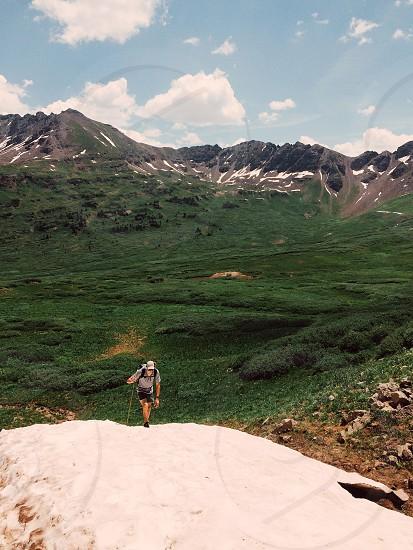 man climbing on mountain and green grass field photo
