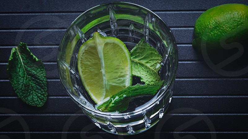 slice of lime and mint leaf on on-rock glass on black wooden table photo