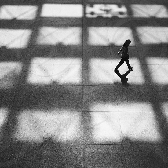 person in white hoodie and black pants walking on grey tiled floors in grayscale photography photo