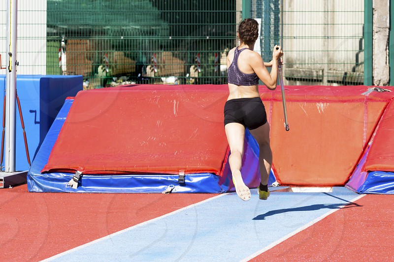 young woman athlete performs the high jump pole vault photo