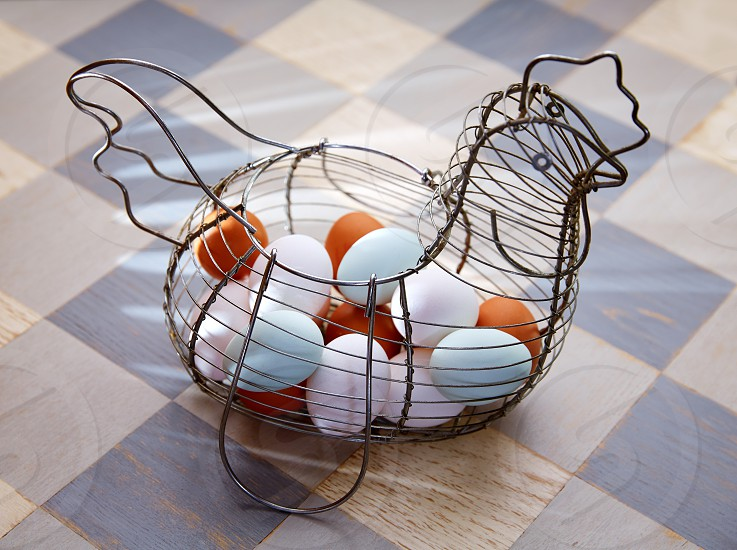 Eggs in a vintage hen shape basket with blue easter white and brown colors photo