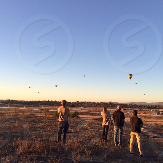 4 man standing watching hot air balloon floating photo