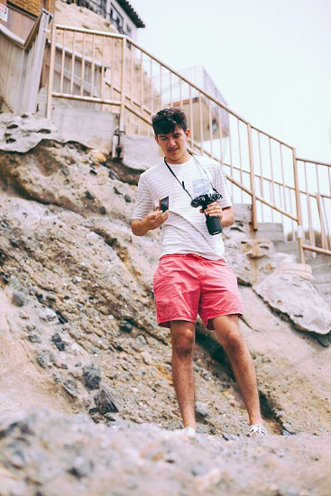 man in red shorts holding black dslr camera photo
