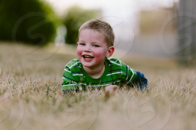 smiling boy in green stripe crew neck t shirt sitting on brown field during daytime photo
