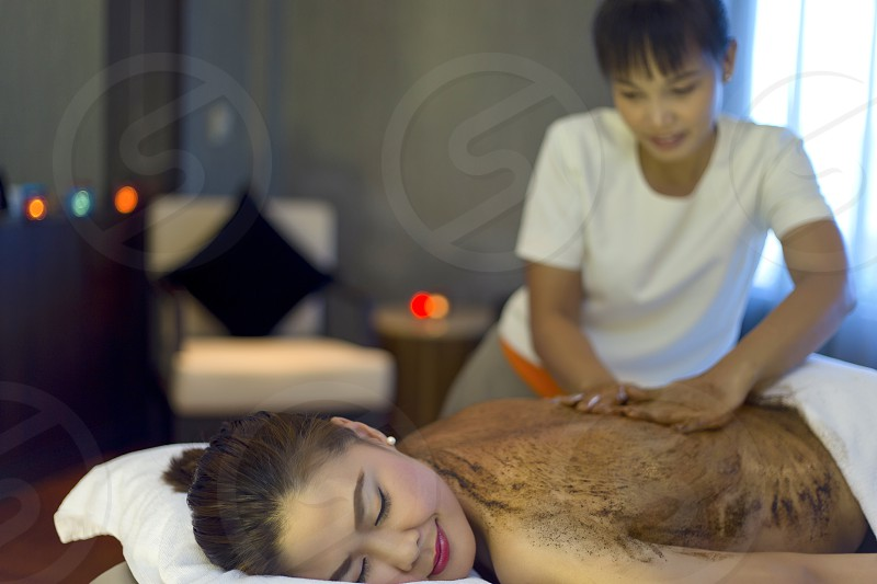 Moment of relaxation at a spa therapist doing scrub coffee massage for a Asian woman model photo
