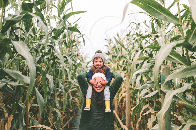 A little boy laughing on his mothers shoulders in a corn field. photo