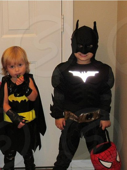girl and boy in black batman suit photo