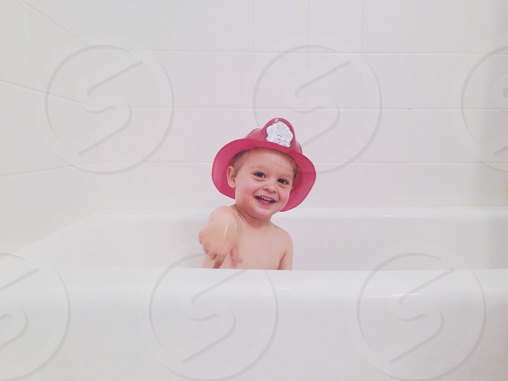 boy with red fireman's hat on white bathtub photo