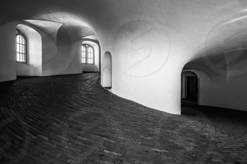 Inside the tower tower Copenhagen Denmark round brick entrance door black and white mysterious dark old antique empty photo